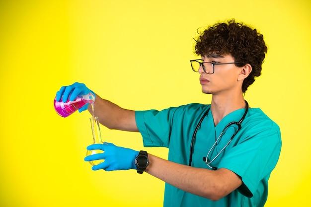 黄色の化学反応を行う医療の制服とハンドマスクの巻き毛の少年。 無料写真