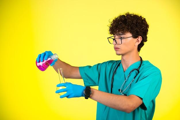 Вьющиеся волосы мальчика в медицинской форме и маски для рук, производящие химическую реакцию с колбами. Бесплатные Фотографии