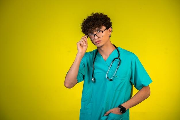 聴診器で医療の制服を着た巻き毛の少年 無料写真