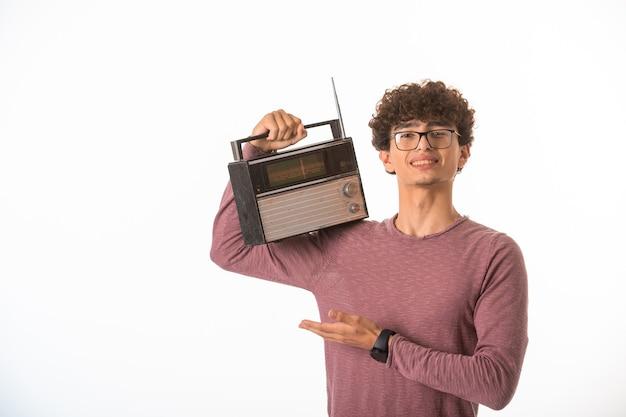 Вьющиеся волосы мальчик в оптических очках, держа на плечах старинное радио. Бесплатные Фотографии