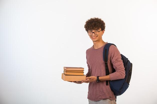 学校の本を保持しているオプティックメガネの巻き毛の少年笑顔と集中しています。 無料写真