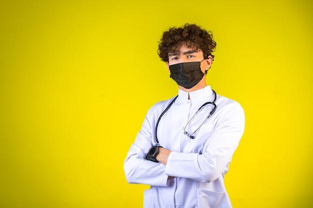 フェイスマスクを着て聴診器で白い医療服の巻き毛の少年 無料写真
