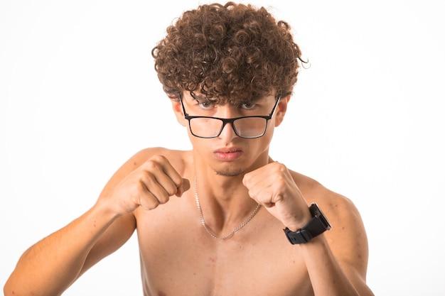 Ragazzo di capelli ricci in vetri optique che perfora con due mani. Foto Gratuite