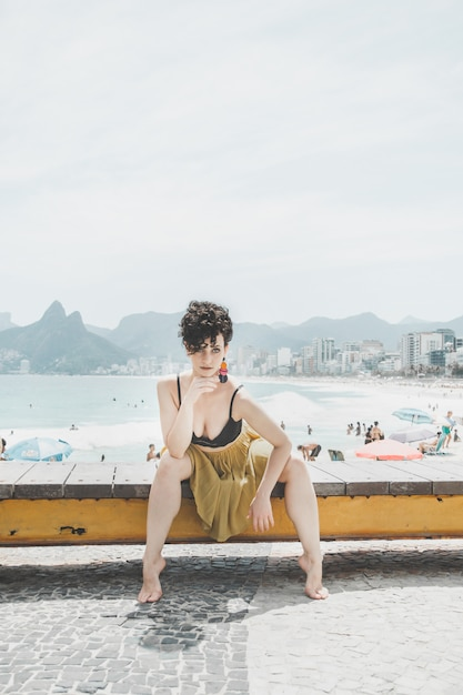 Curly hair model wearing an evening dress and posing on the promenade in rio de janeiro Free Photo