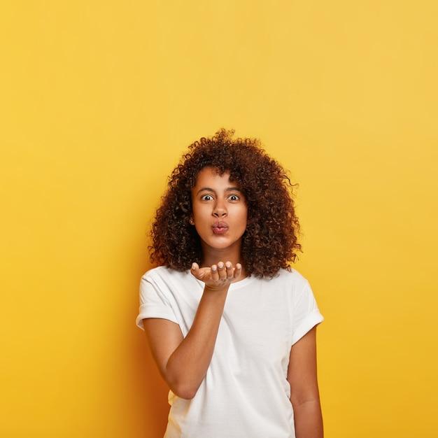 곱슬 머리의 사랑스러운 아프리카 소녀는 공기 키스를 보내고, 입 근처에 손바닥을 잡고 흰색 티셔츠를 입고 열정적 인 Mwah를 불고 입술을 접고 모델을 노란색 벽에 복사하고 위의 공간을 복사합니다. 무료 사진