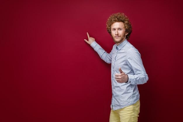 Кудрявый мужчина в рубашке, показывая пустое пространство с указательным пальцем Premium Фотографии
