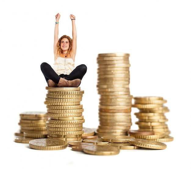 Curly-haired woman sitting on a pile of coins Free Photo