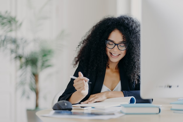 Curly haired woman writes down some information, holds pen, has smile and wears optical glasses Premium Photo