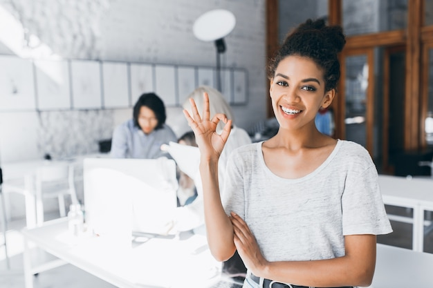 Curly mulatto female student posing with smile and okay sign after difficult test in international university. indoor portrait of african woman work as a manager in office with young asian man behind. Free Photo