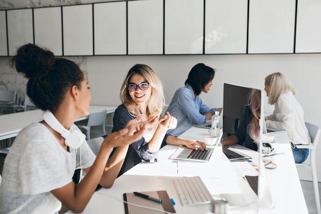 灰色のtシャツを着た巻き毛のムラートの女性が金髪の女性の友人に何かを説明します。一緒にテストの準備をしているラップトップを持つ留学生の屋内の肖像画。 無料写真