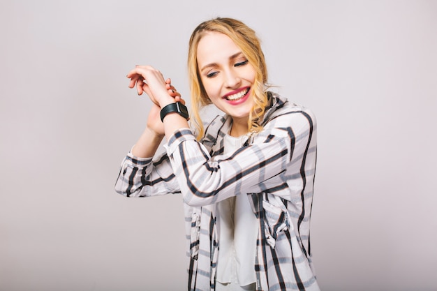 Curly pretty girl in striped trendy shirt listens with interest to the ticking of new black wristwatch. smiling attractive fair-haired young woman posing with hands up isolated. Free Photo