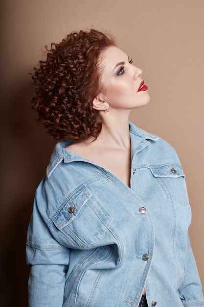 Curly red-haired adult woman in a blue denim shirt Premium Photo