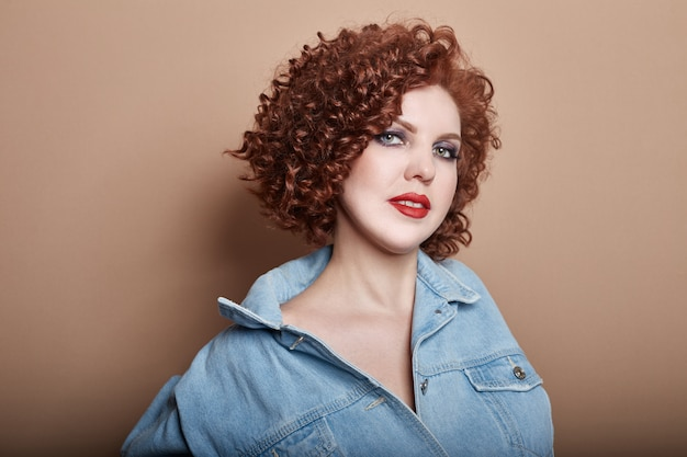 Curly sexy red-haired adult woman in a blue denim Premium Photo