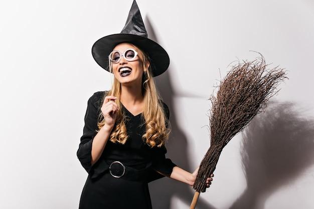 Кудрявая ведьма в очках, выражающая счастье в хэллоуин. крытая фотография смеющейся красивой девушки в костюме волшебника, держащей веник. Бесплатные Фотографии