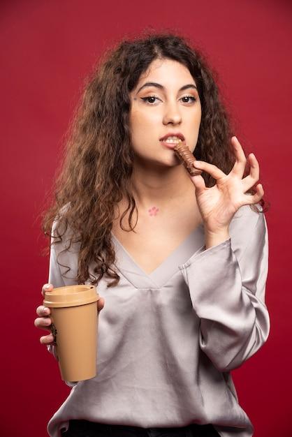 Кудрявая женщина ест шоколад. Бесплатные Фотографии