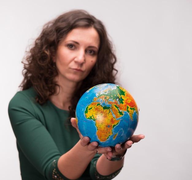 Кудрявая женщина, держащая земной шар на сером фоне Premium Фотографии