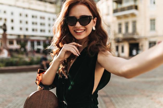 벨벳 드레스에 곱슬 여자는 핸드백을 보유하고 외부 셀카를 걸립니다 무료 사진