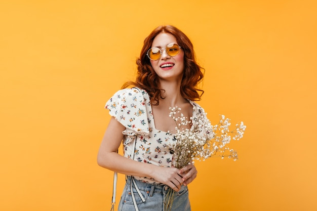 Curly woman in orange sunglasses smiles sweetly and holds wild flowers on orange background. Free Photo