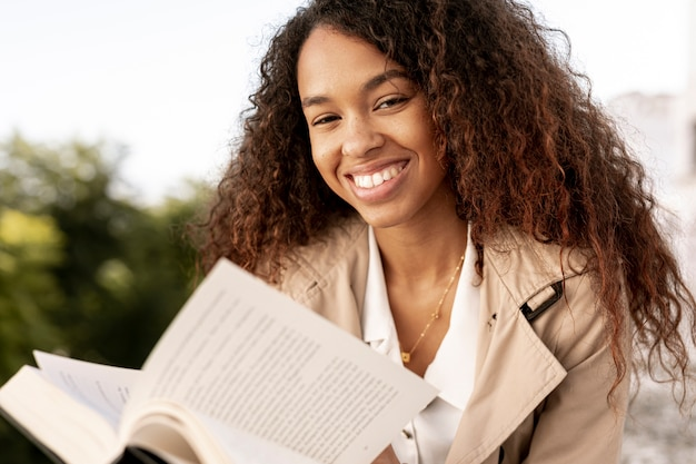 Curly woman reading a book close-up Free Photo