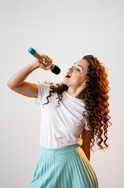 Curly woman singing at a microphone indoors Free Photo