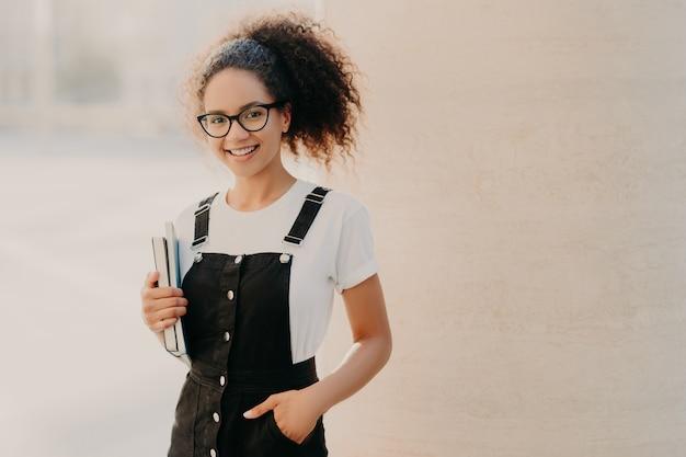 白いtシャツ、サラファンに身を包んだコーマ髪の巻き毛の女性は、ポケットに手を入れて、本と教科書を保持 Premium写真