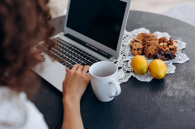 レモンとお茶を飲んで、コンピューターで働くテーブルに座っている巻き毛、若い、魅力的な女の子 Premium写真