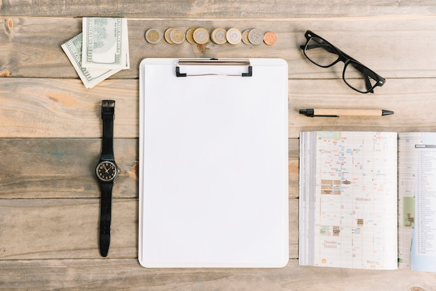 Currency notes and coins with wristwatch; eyeglasses; pen; diary and paper on clipboard over wooden table Free Photo