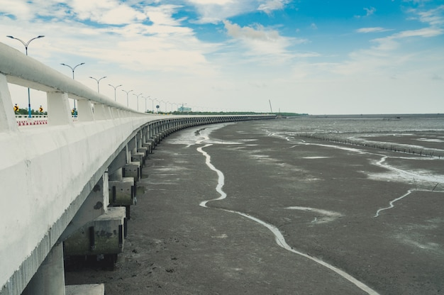 Curved coastal concrete highway road with lower water in the mud beach with blue sky Premium Photo