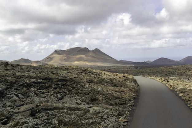 Curva strada circondata da colline sotto un cielo nuvoloso nel parco nazionale di timanfaya in spagna Foto Gratuite