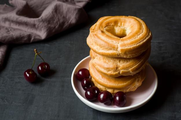 Custard cake rings with cherry on a plate on dark Premium Photo