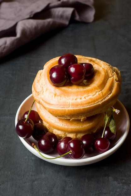 Custard cake rings with cherry on a plate a dark Premium Photo