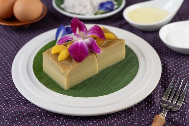 エンドウ豆の花と蘭の白い皿にバナナの葉にカスタード 無料写真