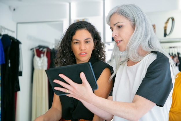 Покупатель и продавец встречаются в магазине модной одежды, сидят вместе и используют планшет, обсуждают одежду и покупки. потребительство или концепция покупок Бесплатные Фотографии