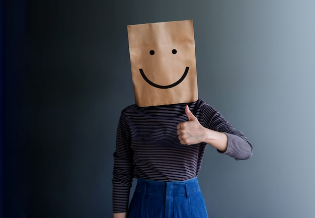 Customer experience or human emotional concept. woman covered her face by paper bag and present happy feeling by drawn line cartoon and body language Premium Photo