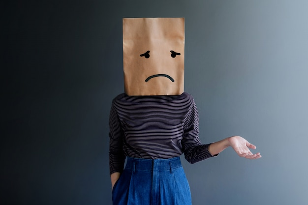 Customer experience or human emotional concept. woman covered her face by paper bag and present sadness feeling and disappointed by drawn line cartoon and body language Premium Photo