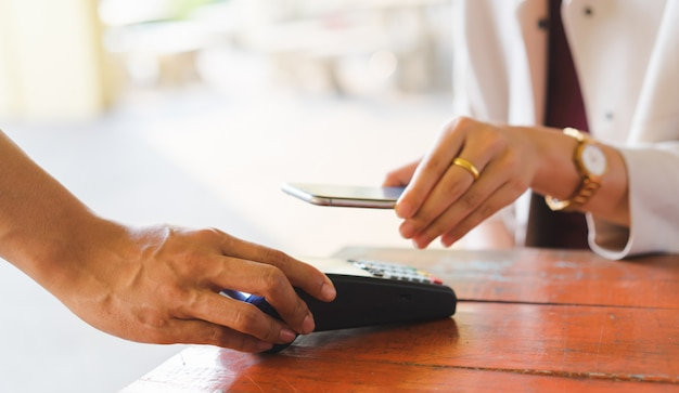 Customer hand using smartphone for paying bill by using payment machine at table Premium Photo
