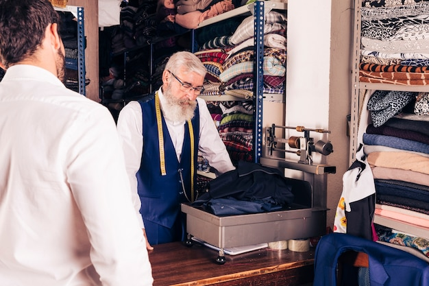 Customer looking at senior male tailor weighing the fabric in the shop Free Photo