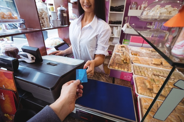 Cliente che effettua il pagamento tramite carta di credito Foto Gratuite