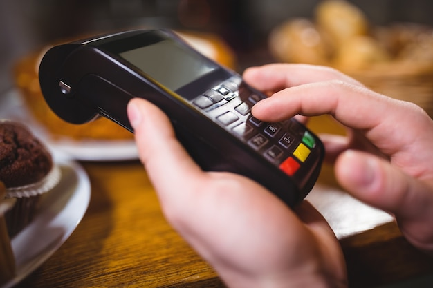 Client Can Download Photos After Payment: Customer Making Payment Through Payment Terminal At