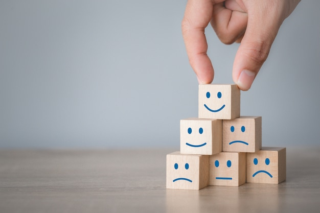 Customer pressing smiley face emoticon on wood cube, service rating, satisfaction concept. Premium Photo