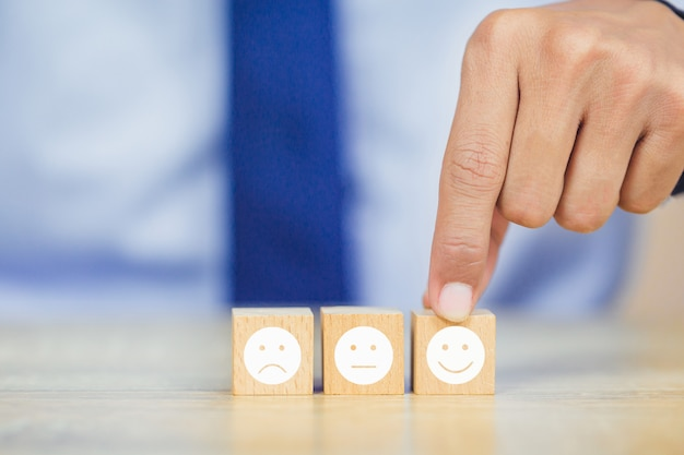 Customer pressing smiley face emoticon on wood cube Premium Photo