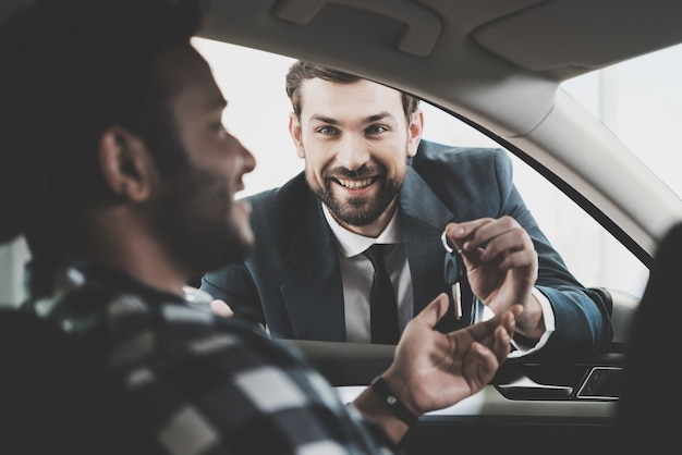 Customer receives keys from manager car deal. Premium Photo