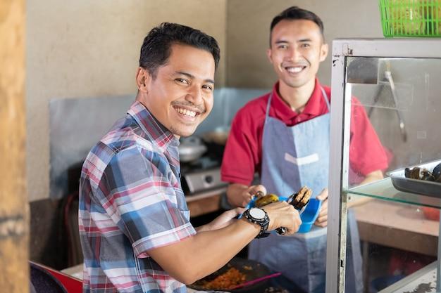屋台の背景のトレイを持って売り手が出されるとき、顧客はおかずを選んで微笑む Premium写真