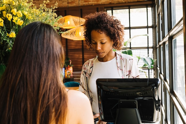 Customer standing in front of female cashier in the restaurant Free Photo
