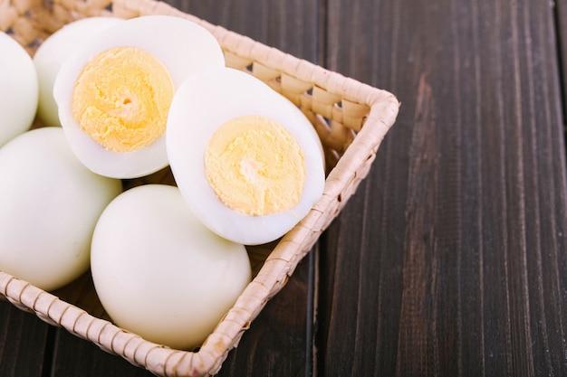Cut boiled eggs lie in wooden besket on dark dinner table Free Photo