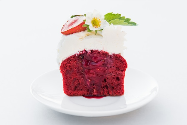 Cut cupcake red velvet with strawberry and cream on white plate. close up Premium Photo