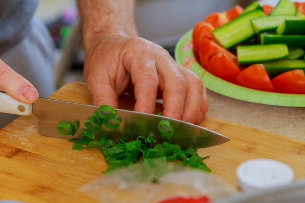 Cut Green Onion With A Kitchen Knife On A Wooden Cutting