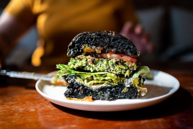 Cut half of broccoli quinoa charcoal burger topped with guacamole, mango salsa and fresh salad served on a white plate. creative vegan meal for vegetarians. Premium Photo