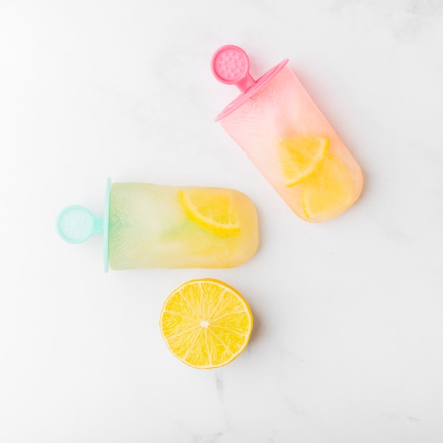 Cut lemon and fresh ice popsicle with citrus on colorful sticks Free Photo