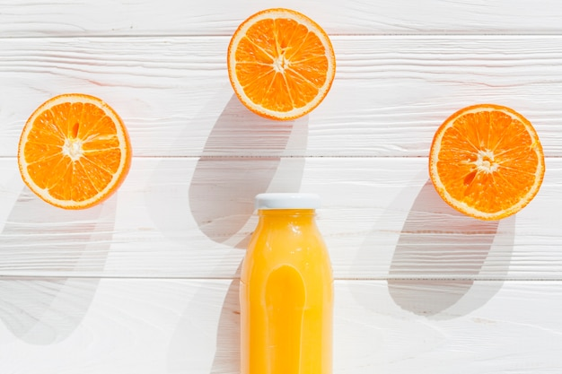 Cut oranges with bottle of juice Free Photo